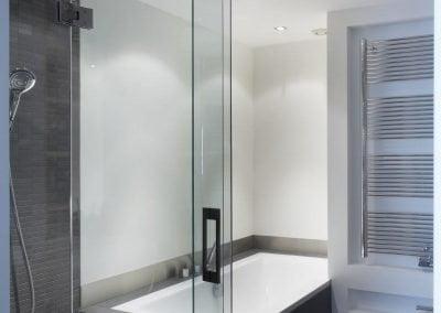 Badkamer met bad douche en toilet en dubbele wastafel