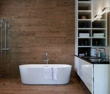 Badkamer met houtlook tegels en vrijstaand bad